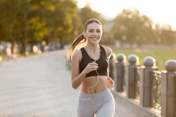 happy millennial girl running on quay and listening to music - exercise stock photos and pictures