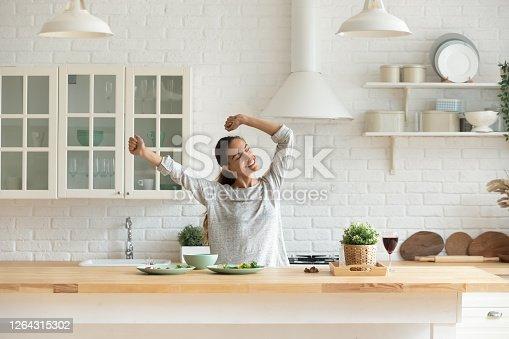 istock Happy millennial woman have fun cooking breakfast in kitchen 1264315302