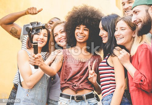 Happy millennials friends making video feed with smartphone outdoor - Young people having fun with new technology trends - Youth lifestyle and social media concept - Focus on black african girl face