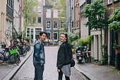 Two young adults are walking down a street in Amsterdam. they are turning to look at the camera.