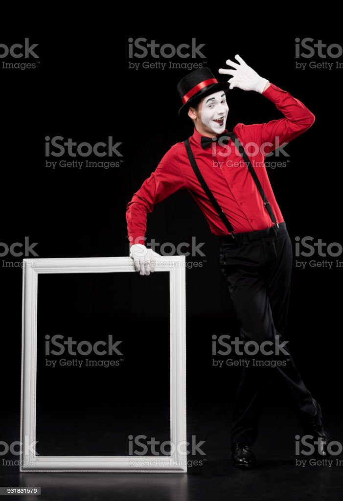 happy mime leaning on frame and waving hand isolated on black stock photo