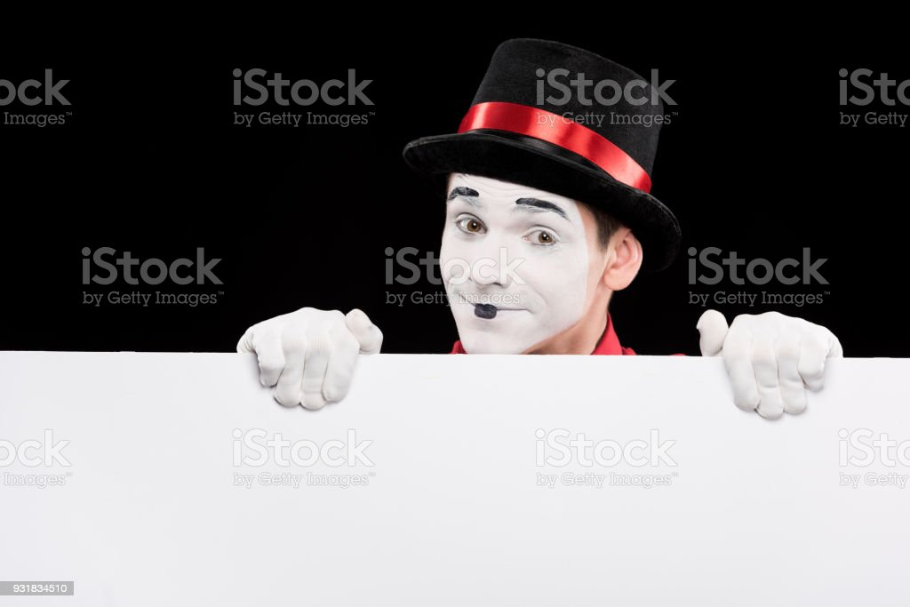 happy mime looking out from empty board isolated on black stock photo