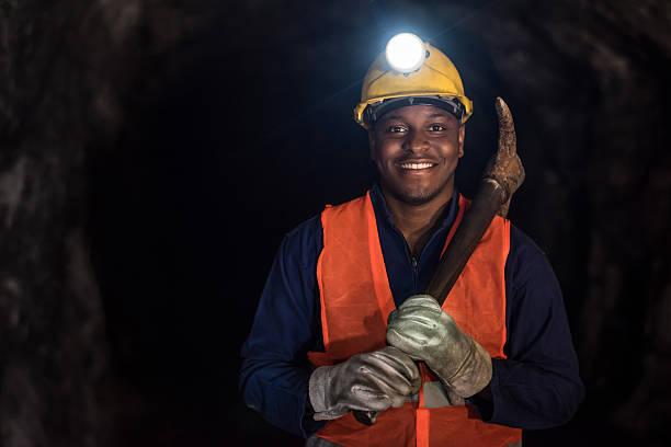 Happy miner working at a mine underground stock photo