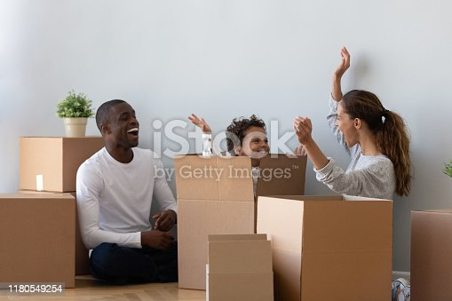 Happy mixed race ethnicity family and cute kid son playing on moving day, young parents tenants renters home owners having fun with child jump out of box unpack laughing enjoy relocation in new flat