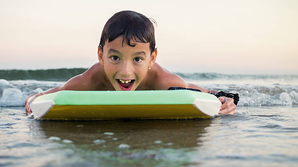 Happy mixed race boy uses boogie board in the ocean stock photo