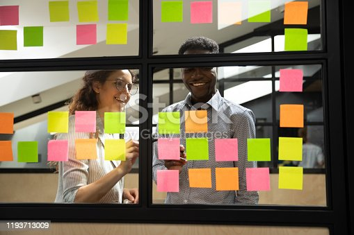 1147760705 istock photo Happy mixed race colleagues standing near window glass board. 1193713009
