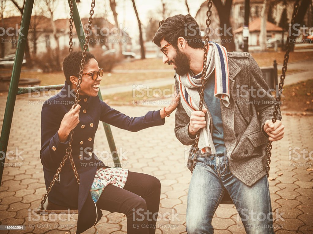 happy mixed race couple playing on swing stock photo