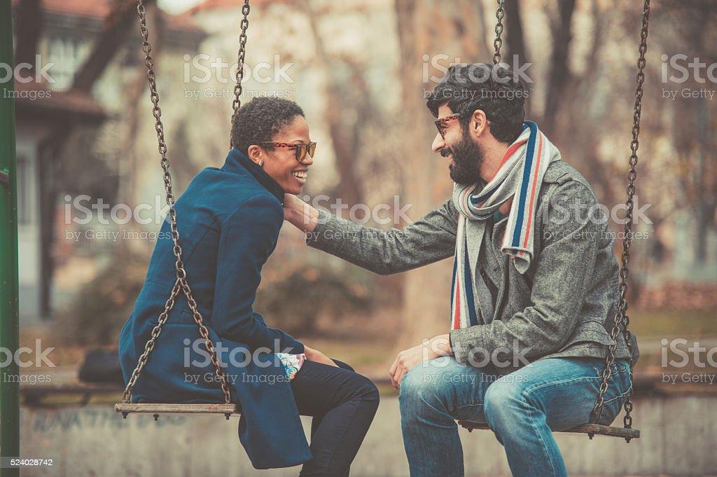 happy mixed race couple playing on swing stock photo