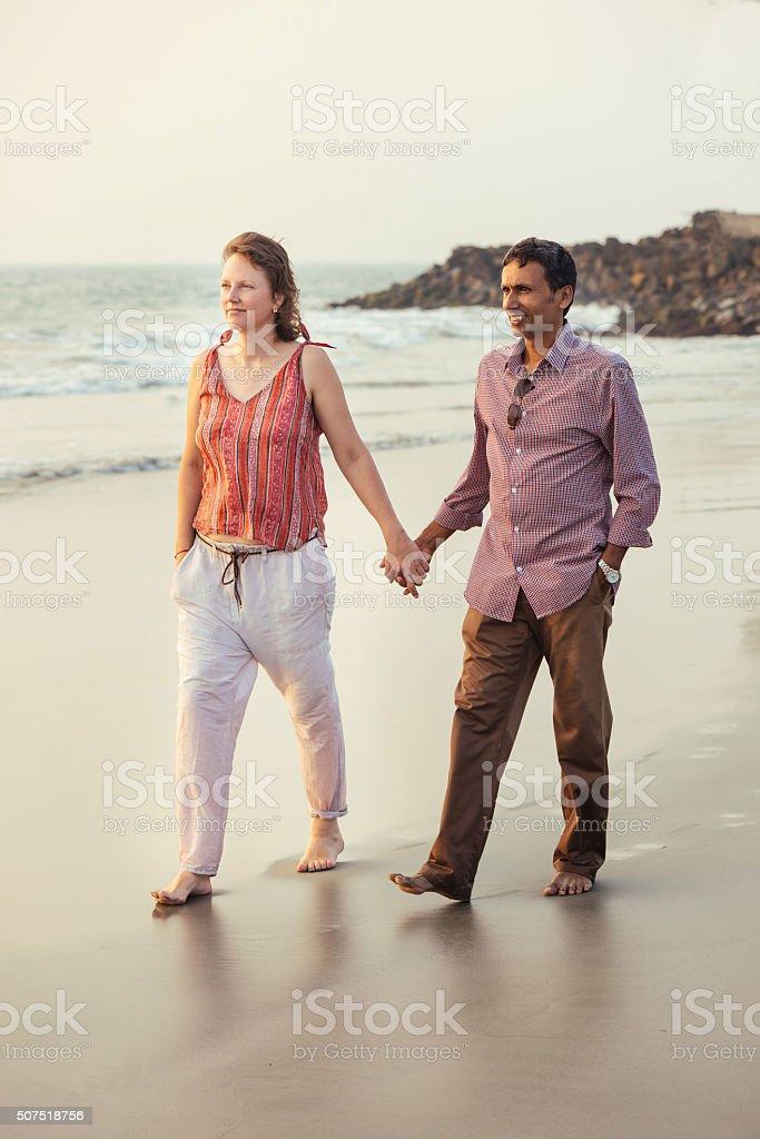 Happy mixed race couple walking on the beach stock photo