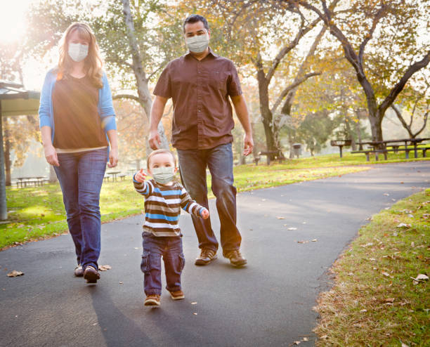 Happy Mixed Race Ethnic Family Walking In The Park Wearing Medical Face Mask Happy Mixed Race Ethnic Family Walking In The Park Wearing Medical Face Mask. latin american and hispanic ethnicity stock pictures, royalty-free photos & images