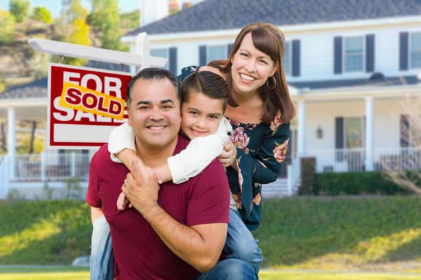 Glücklich gemischte Rennen Familie vor dem Haus und verkauft zum Verkauf Immobilien Zeichen – Foto