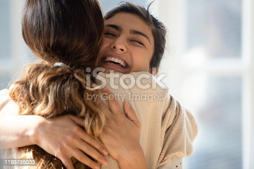 Head shot close up happy mixed race girl cuddling smiling indian female friend. Overjoyed excited best buddies emracing hugging, greeting each other with success, true strong friendship concept.