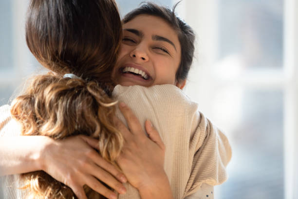 Happy mixed race girl cuddling smiling indian female friend. stock photo