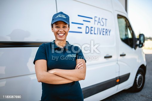 Cheerful female delivery driver in uniform standing next to van hired for expert independent package transport.