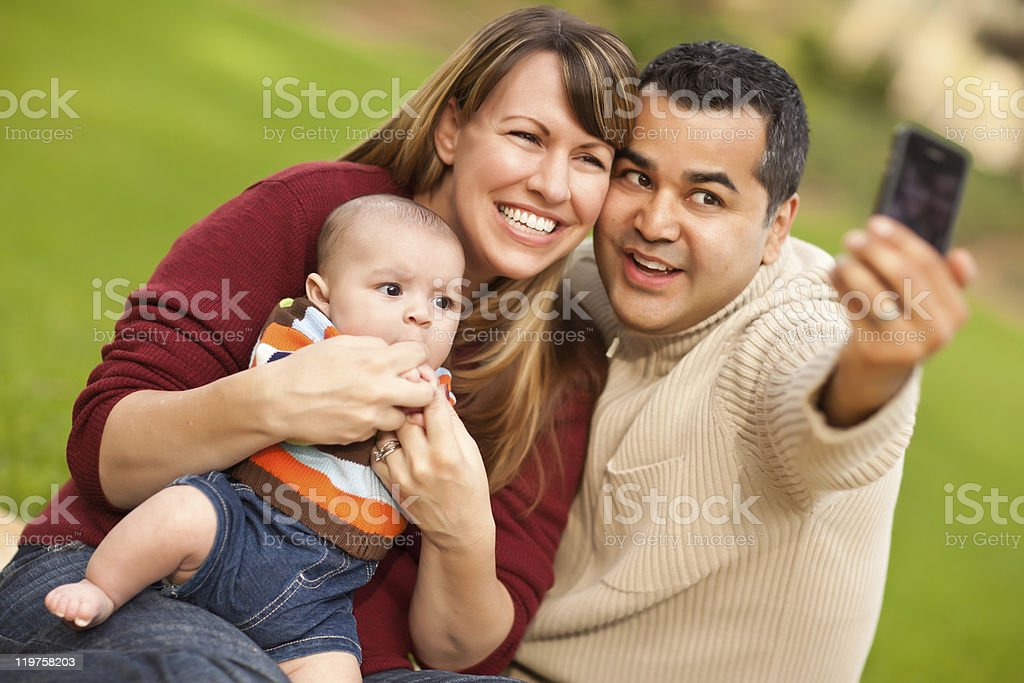 Happy Mixed Race Parents and Baby Boy Taking Self Portraits royalty-free stock photo