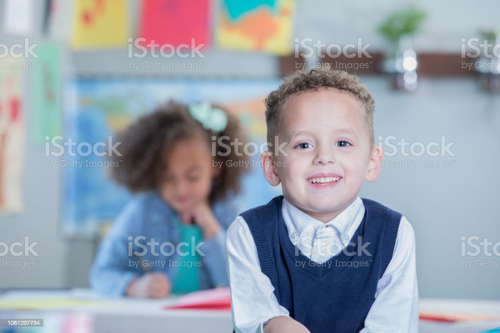 Happy mixed race preschool age little boy looks at the camera and...