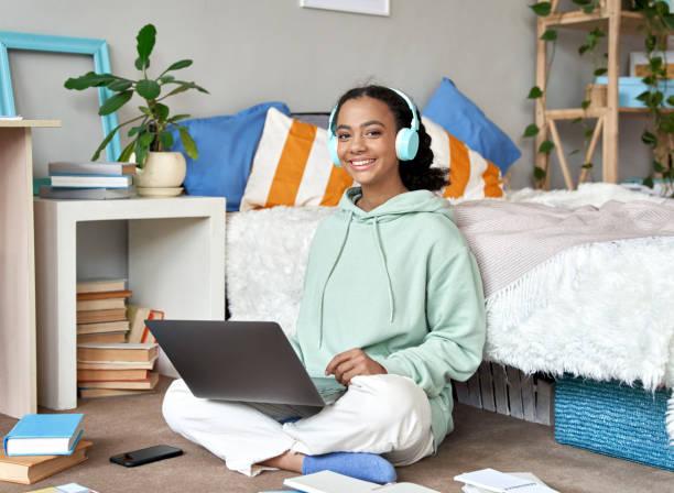 幸せな混合レース十代の女子高生は、ヘッドフォンを身に着けているリモートeは、カメラを見て寝室でラップトップを使用して学習。遠隔教育の授業、自宅でオンラインで勉強。 - gen z ストックフォトと画像