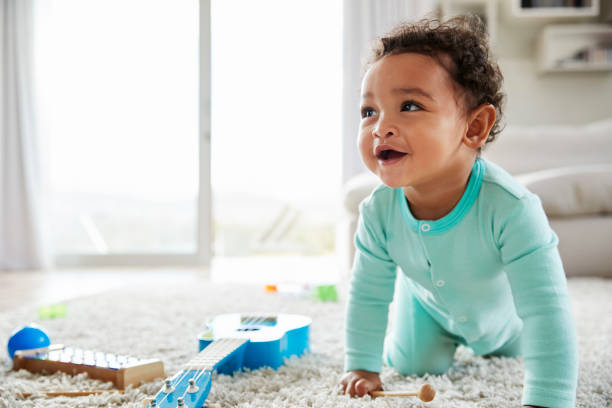 Happy mixed race toddler boy crawling in sitting room Happy mixed race toddler boy crawling in sitting room baby clothing stock pictures, royalty-free photos & images