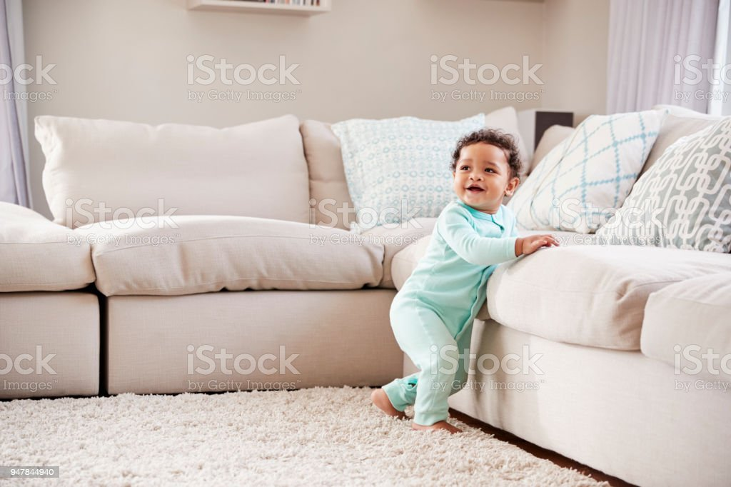 Happy mixed race toddler boy playing in sitting room stock photo