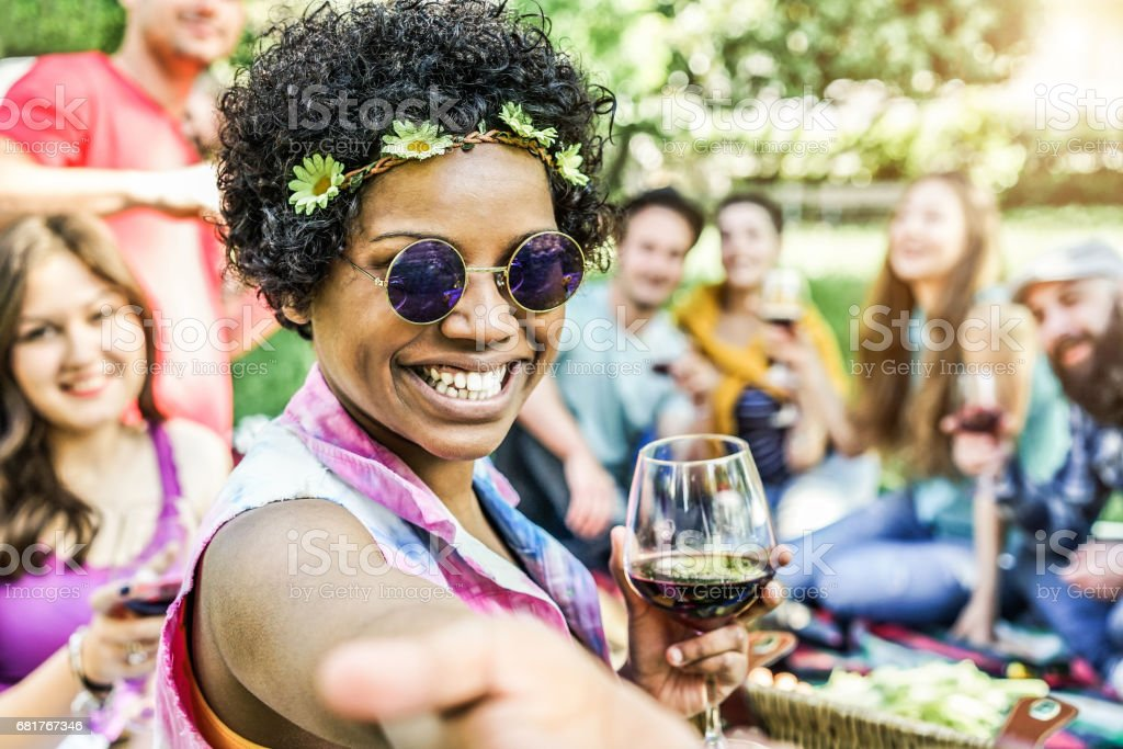 Happy mixed race woman taking selfie at picnic outdoor with her friends - Young trendy people having fun while eating and toasting red wine - Youth and friendship concept - Warm contrast filter stock photo