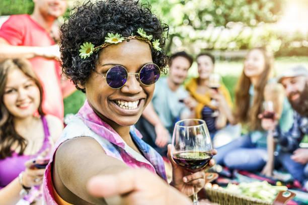 glad blandad ras kvinna tar selfie på picknick utomhus med hennes vänner - trendiga ungdomar ha kul när du äter och rosta rött vin - ungdom och vänskap koncept - varma kontrast filter - happy indie pop bildbanksfoton och bilder