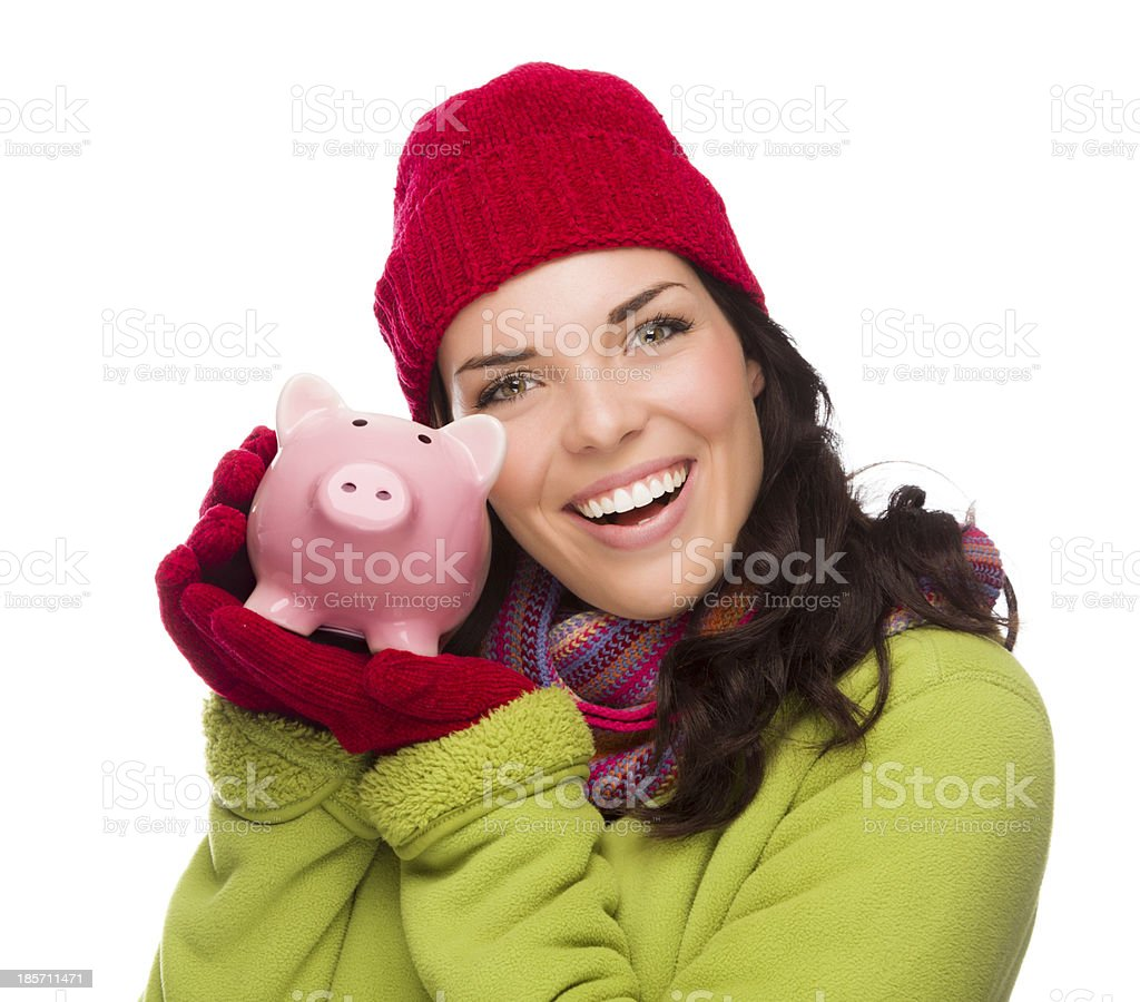 Happy Mixed Race Woman Wearing Winter Hat Holding Piggy Bank royalty-free stock photo