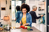 Beautiful mixed race mother and daughter  preparing delicious and healthy salad in modern kitchen. African American woman cutting fresh vegetables, while mature woman taking groceries from the fridge.