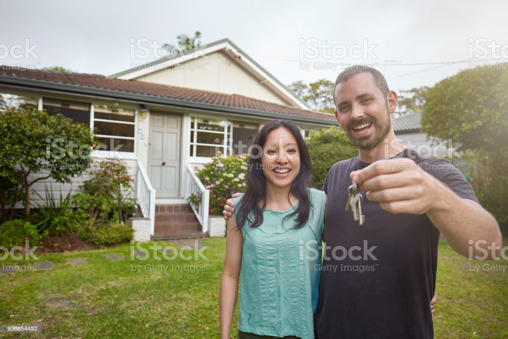 Happy mixed-race couple showing the keys of the new house stock photo