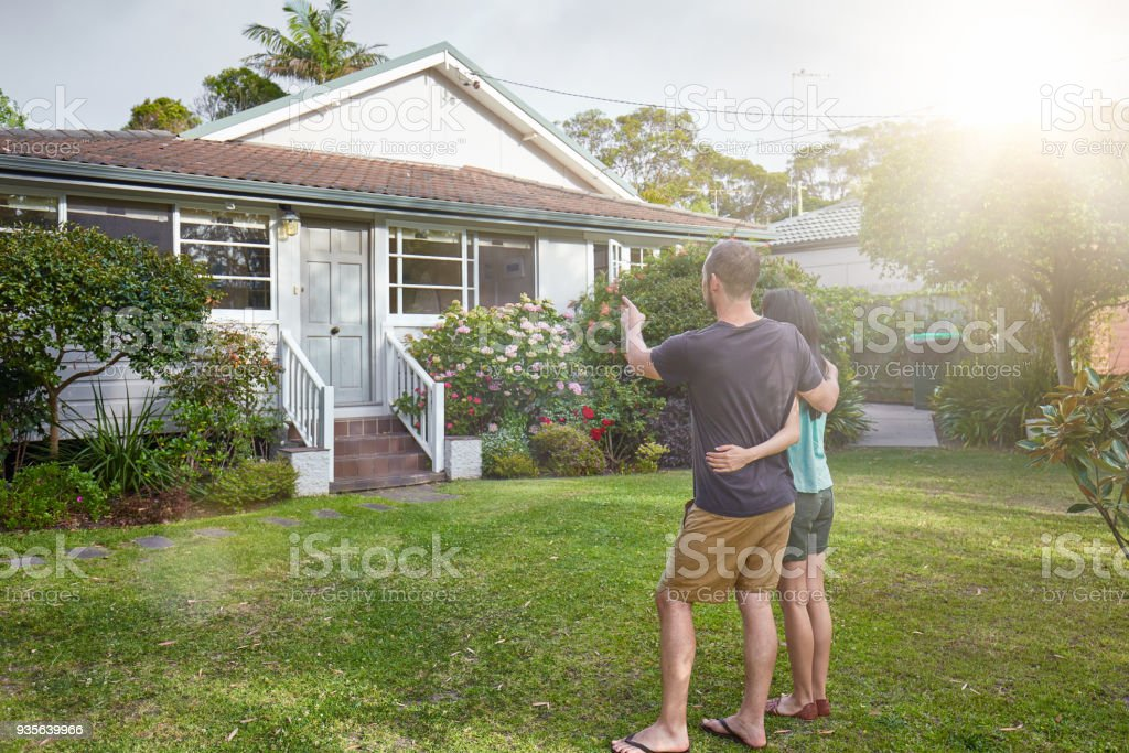 Happy mixed-race couple standing in front of house stock photo