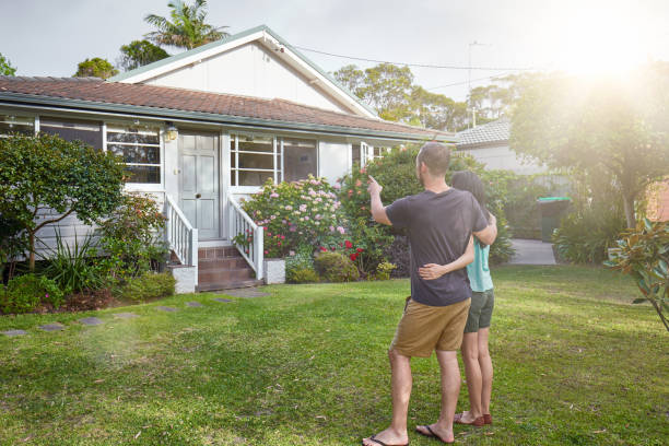 Happy mixed-race couple standing in front of house Happy mixed-race couple standing in front of house. house rental stock pictures, royalty-free photos & images
