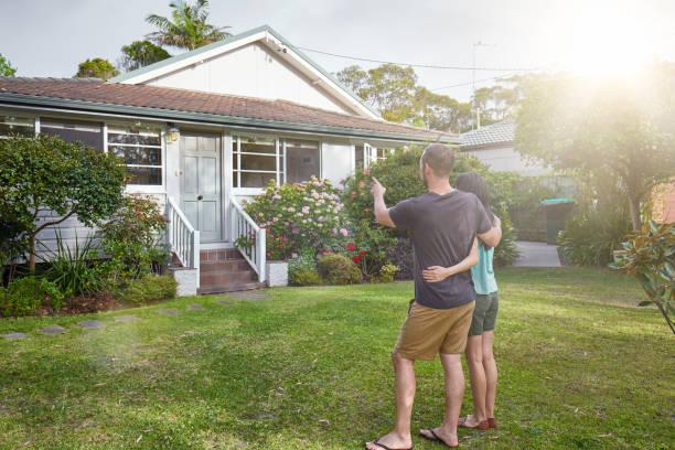 pie de la feliz pareja de mestizos frente a casa - casa alquilada fotografías e imágenes de stock