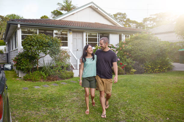 Happy mixed-race couple walking outside their front yard garden stock photo
