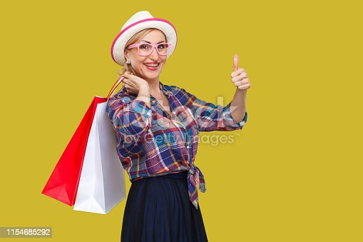 Happy modern aged woman in white hat and in checkered shirt standing, holding shopping bags and showing thumbs up with toothy smile, looking at camera. Indoor, studio shot, yellow background, isolated