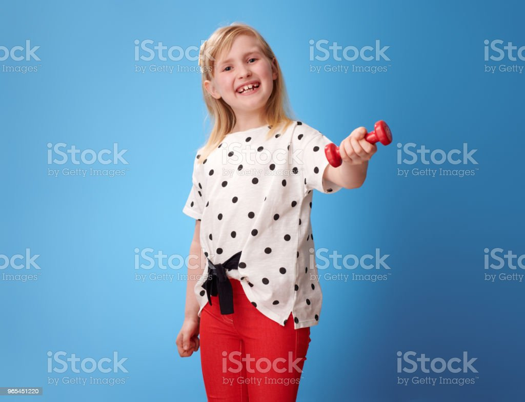happy modern child in red pants on blue showing dumbbell zbiór zdjęć royalty-free