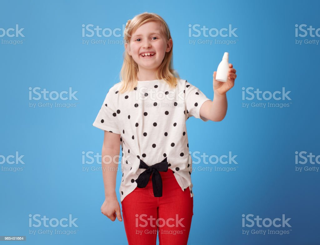 happy modern child in red pants on blue showing nasal drops zbiór zdjęć royalty-free