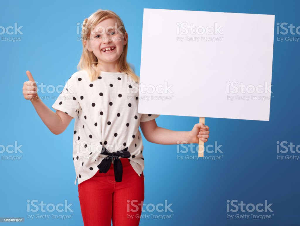 happy modern child showing blank poster and thumbs up on blue zbiór zdjęć royalty-free