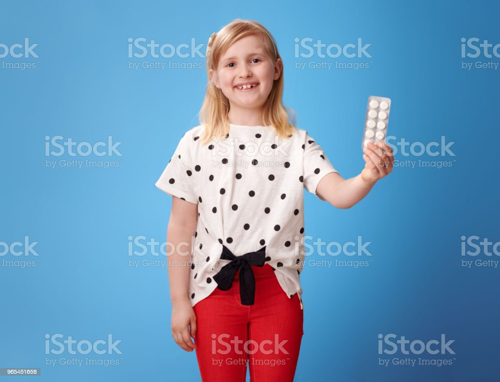 happy modern child showing medicine in blister pack on blue royalty-free stock photo