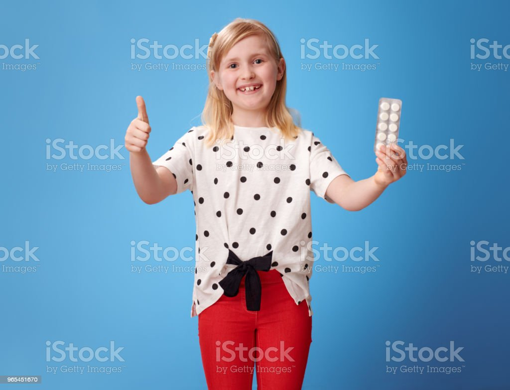 happy modern child showing thumbs up and and pill on blue zbiór zdjęć royalty-free