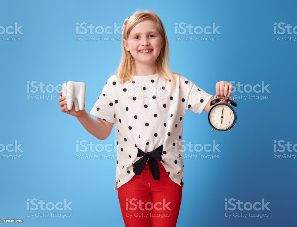 happy modern child showing tooth and alarm clock on blue royalty-free stock photo