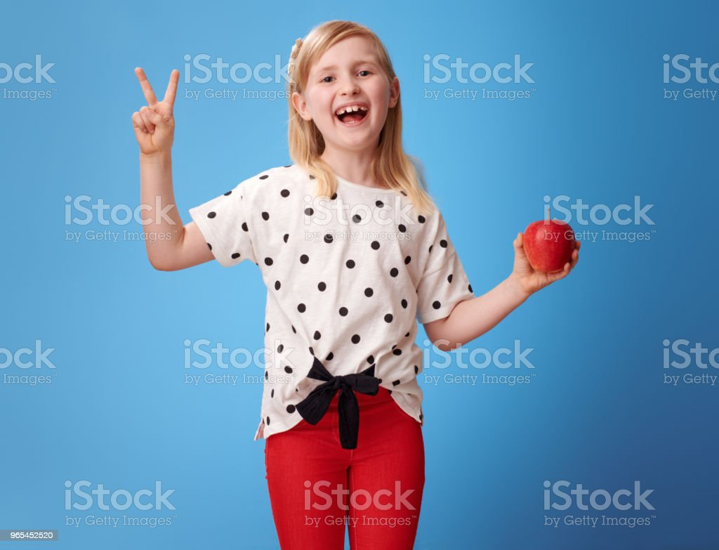 happy modern child with an apple showing victory on blue zbiór zdjęć royalty-free