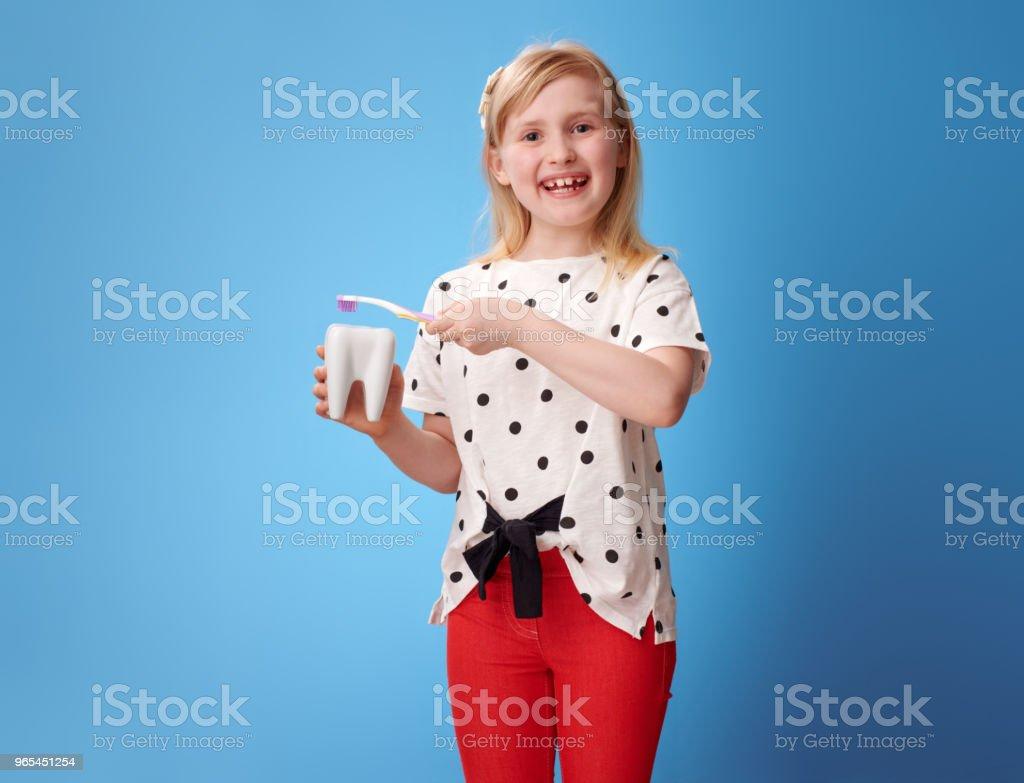 happy modern girl brushing tooth with toothbrush on blue zbiór zdjęć royalty-free