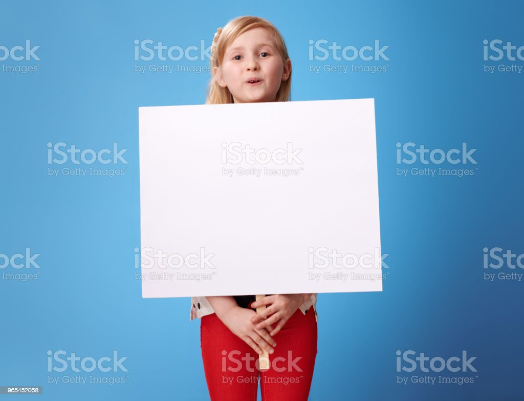 happy modern girl in red pants on blue showing blank poster royalty-free stock photo