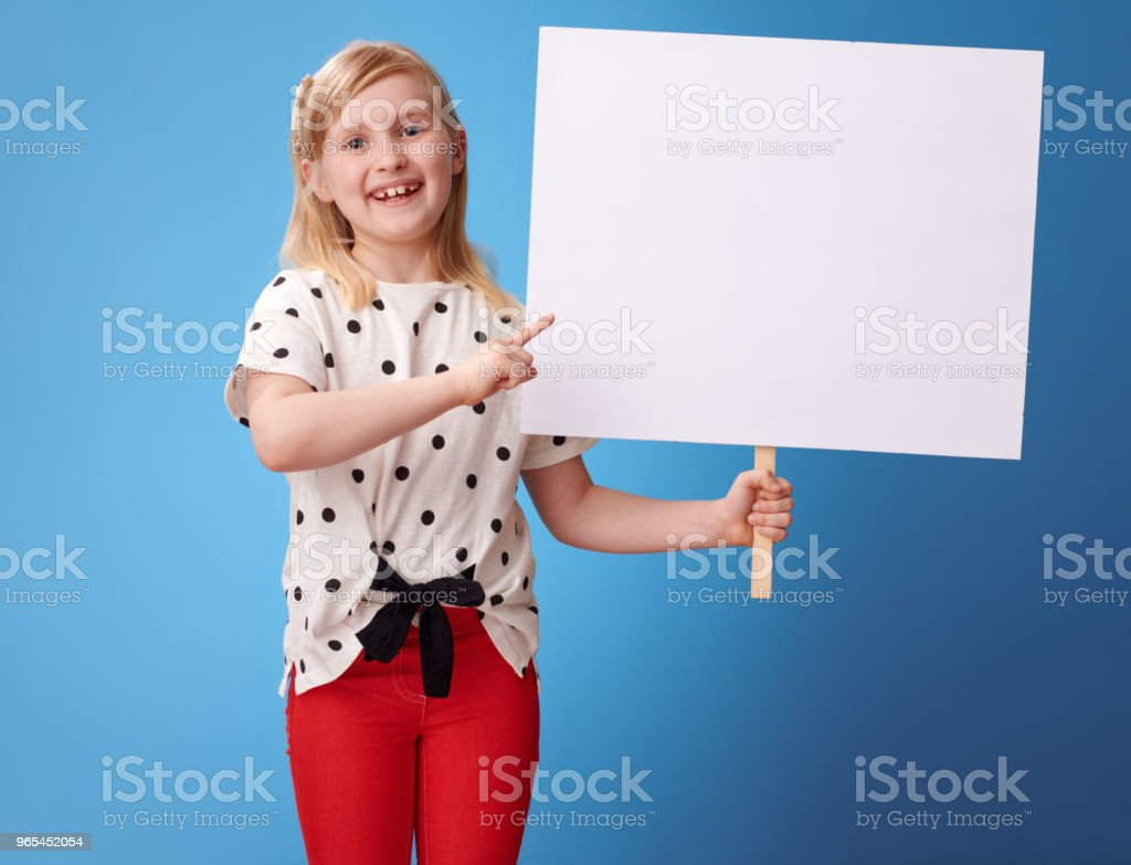happy modern girl pointing at blank placard on blue royalty-free stock photo