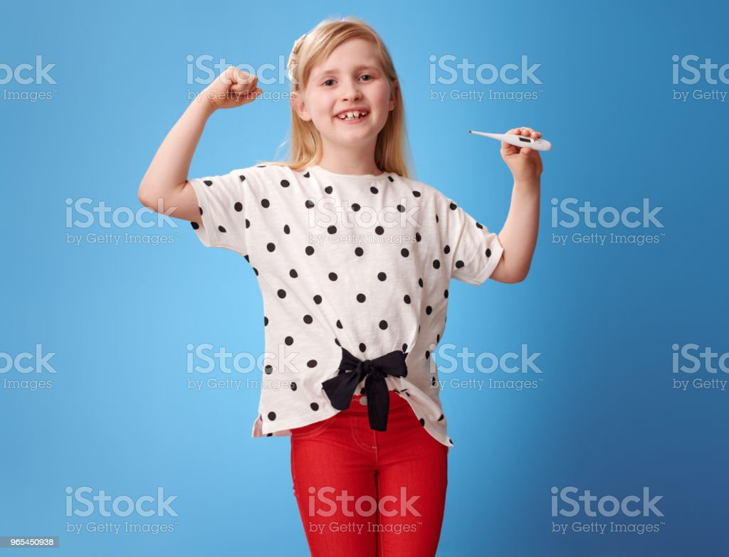 happy modern girl showing biceps and thermometer on blue royalty-free stock photo