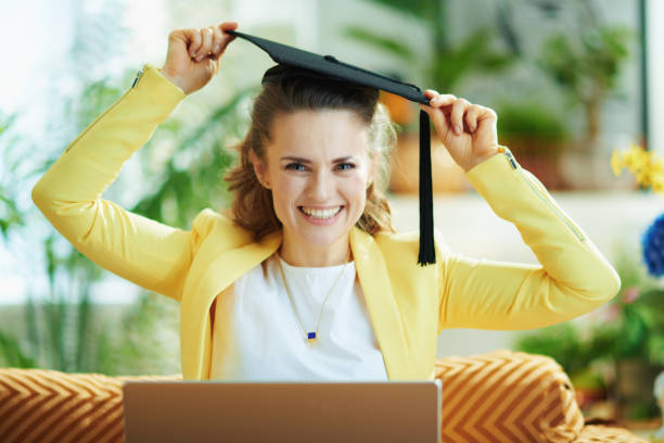 happy modern housewife with graduation cap and laptop stock photo