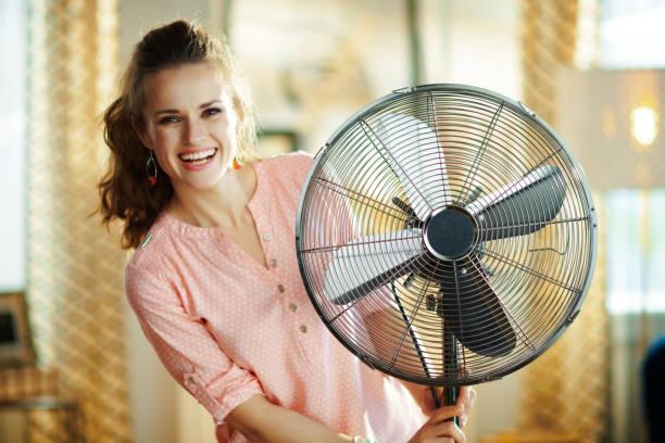 Glückliche moderne Frau in der Nähe von elektrischem Boden stehenden Ventilator – Foto