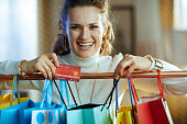 happy modern woman in white sweater and skirt with credit card near colorful shopping bags hanging on copper clothes rail.