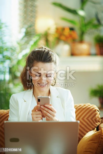 happy modern woman in white blouse and jacket with laptop and smartphone texting in the modern living room in sunny day.