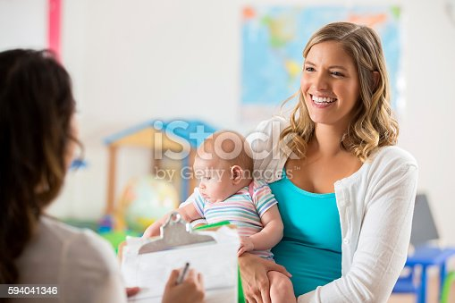 istock Happy mom and baby getting tour of a daycare center 594041346