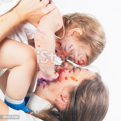 istock Happy mom and baby playing with painted face by paint 585313490